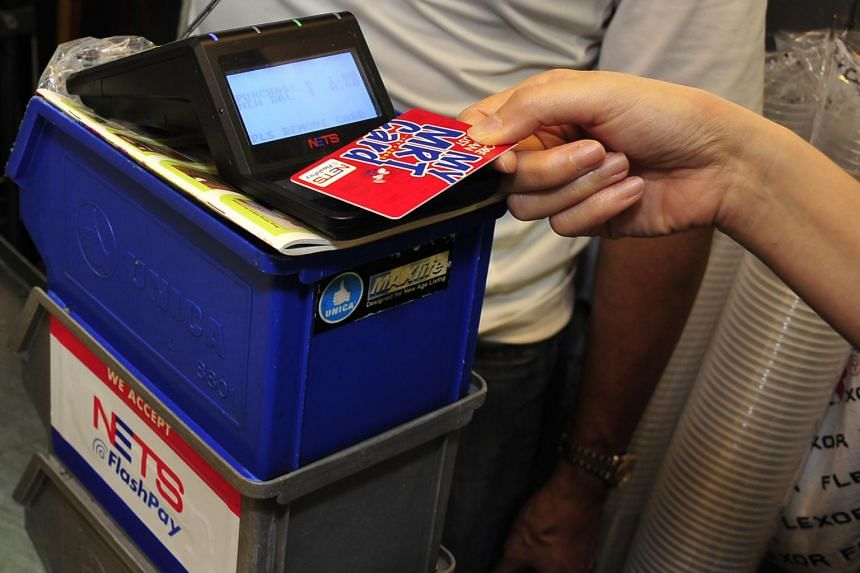 A customer using a Nets flashpay card to pay at a stall at Beo Crescent Market and Food Centre.