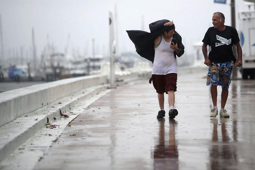 Local residents walk through strong winds before the approaching Hurricane Harvey in Corpus Christi, Texas on Aug 25, 2017.