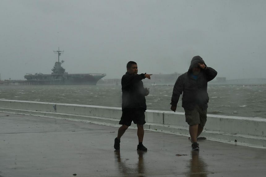 Local residents walk through strong winds beside the Lexington aircraft carrier before the approaching Hurricane Harvey in Corpus Christi, Texas on Aug 25, 2017.