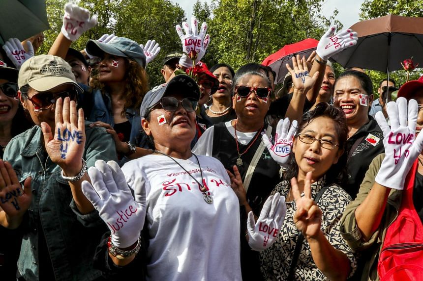 Supporters of former Thai Prime Minister Yingluck Shinawatra wait for her arrival at the Supreme Court's Criminal Division for Holders of Political Positions, in Bangkok, on Aug 25, 2017.