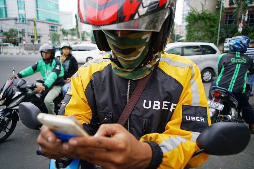 An Uber rider checks his smartphone as a Go-Jek rider (left) ferries a passenger in the background and a GrabBike rider navigates traffic in Jakarta, Indonesia. Asean countries can use digitisation and Internet technology to improve energy and resource us