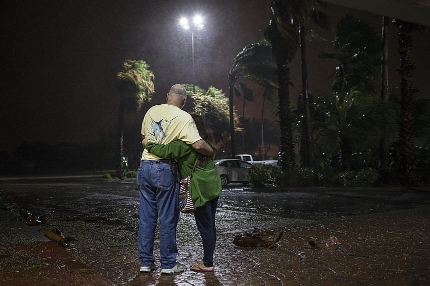 A couple who were evacuated from Aransas Pass, Texas, looking out at the heavy rain from a hotel in Corpus Christi, Texas, last Friday.