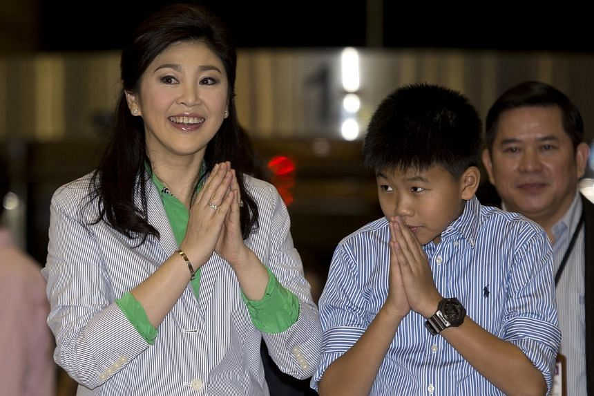 Yingluck Shinawatra and son Supasek Amornchat at Suvarnabhumi Airport in 2014. The former premier left her only child in the care of her businessman husband last week before leaving the country, said a source.