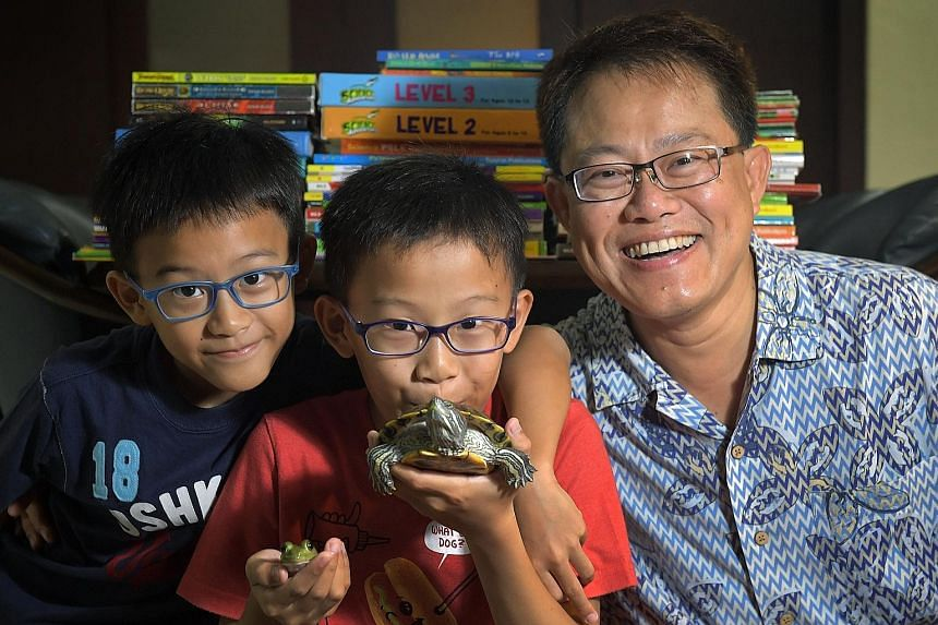 """Kayden, nine; Kieran, with his pet turtle and pet frog; and their father Alvin Lee, 52. Said Kieran: """"I just want an hour of homework. Otherwise, it piles up and when I look at the stack of work, I feel very stressed out."""" Eleven-year-old Kieran Lee"""