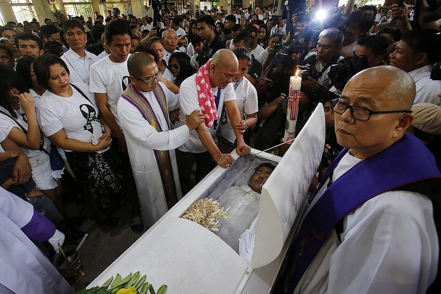 Filipinos gather to demand justice for Kian, The teenager's death may have struck a chord with many because of his age and the way he was killed. Mr Saldy de los Santos being comforted by his wife Lorenza (half-hidden), as he mourns at the coffin of