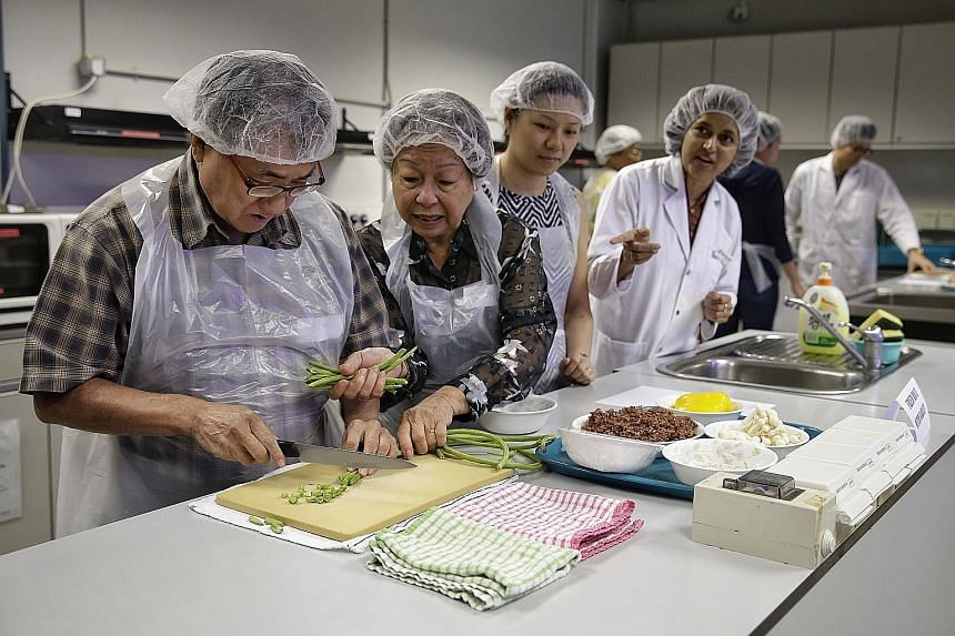 Participants such as Mr Michael Lee (left) and Madam Helen Chua (second from left), both Diabetic Society of Singapore members, preparing ingredients during the cooking session for the course on nutrition therapy for the prevention and management of