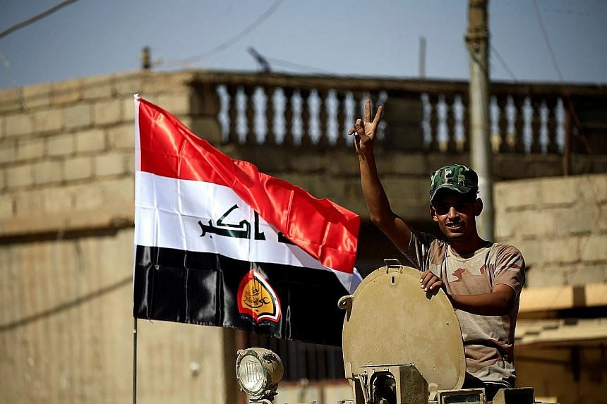 """A member of Shi'ite Popular Mobilisation Forces flashing the victory sign in Tal Afar yesterday. The Counter- terrorism Service """"liberated the citadel neighbourhood"""", the Iraqi joint operations command said. A clash between joint troops of Iraqi army"""