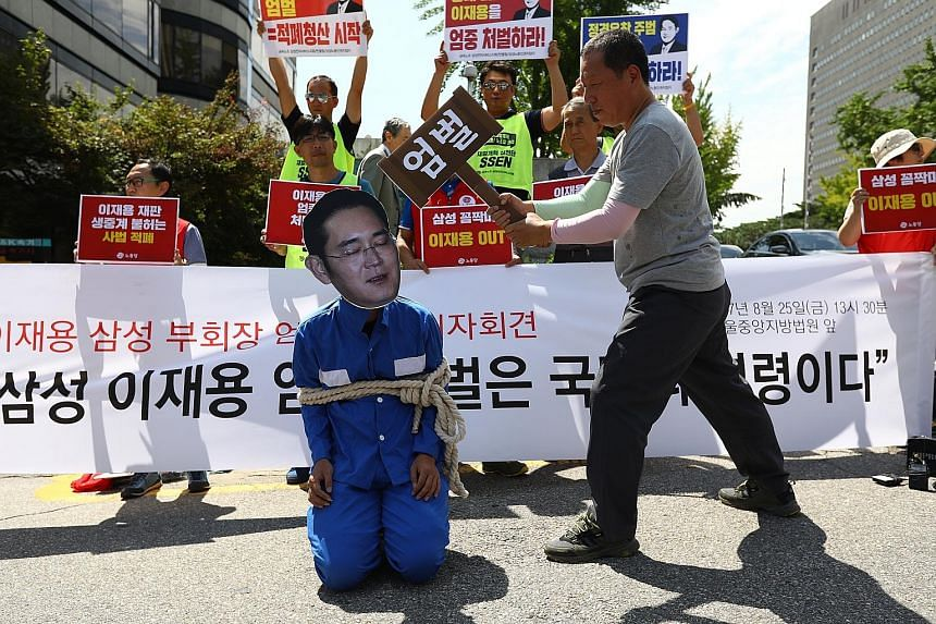 Demonstrators protesting against Samsung's de facto leader Lee Jae Yong on Friday outside the Seoul Central District Court where he was sentenced.