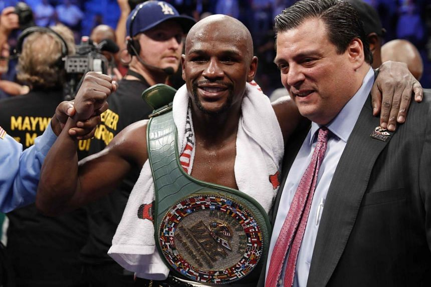 Floyd Mayweather Jr celebrates with the belt and President of the WBC Mauricio Sulaiman after winning the fight.
