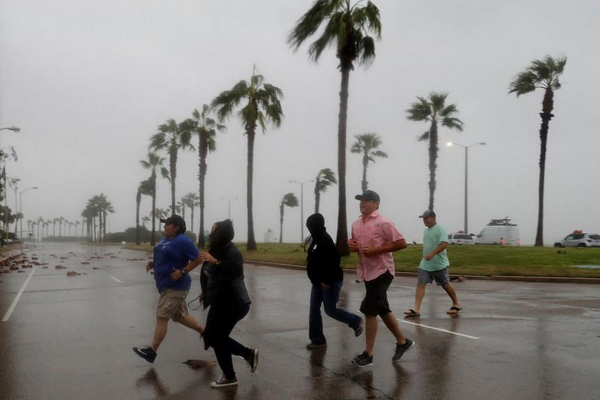 A group of people race across the street as winds from Hurricane Harvey escalated in Corpus Christi, on Aug 25, 2017.