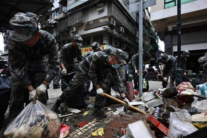 Chinese People's Liberation Army soldiers help clear debris from a street in Macau on Aug 25, 2017.