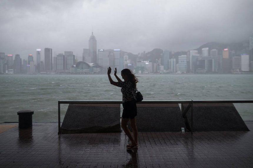 A woman raises her hands to block the rain on the Victoria Harbour waterfront in Hong Kong, on Aug 27, 2017.