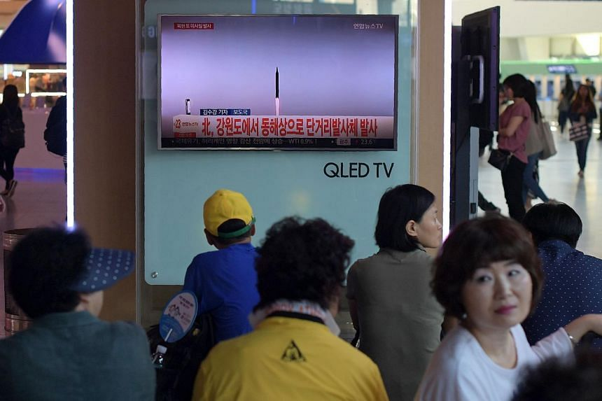 People are seen past a television screen showing news footage of a North Korean missile launch, at a railway station in Seoul on Aug 26, 2017.