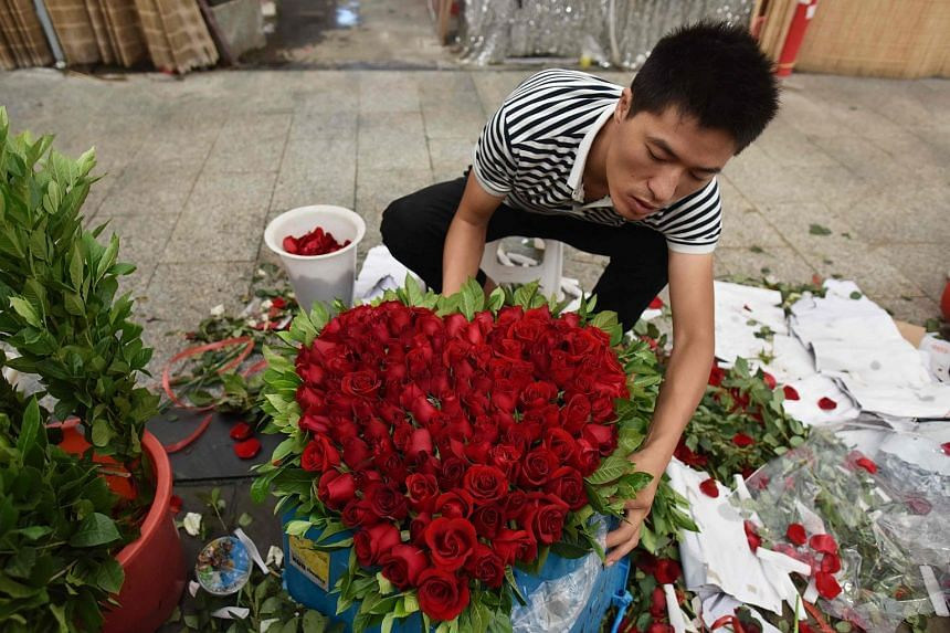 A florist preparing a heart-shaped bouquet of roses at a flower market in Beijing on Aug 25, 2017.