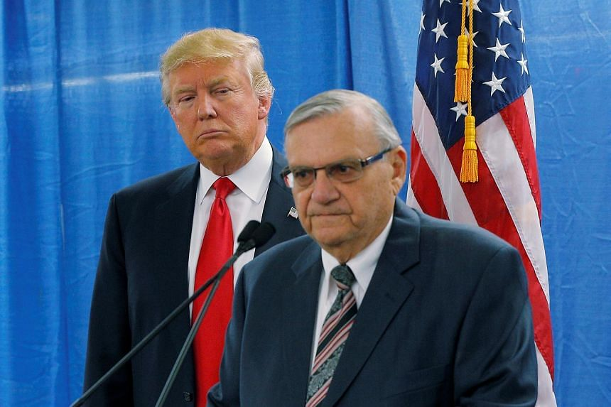 Donald Trump listens as Joe Arpaio (right) speaks to reporters before a campaign rally in Marshalltown, on Jan 26, 2016.