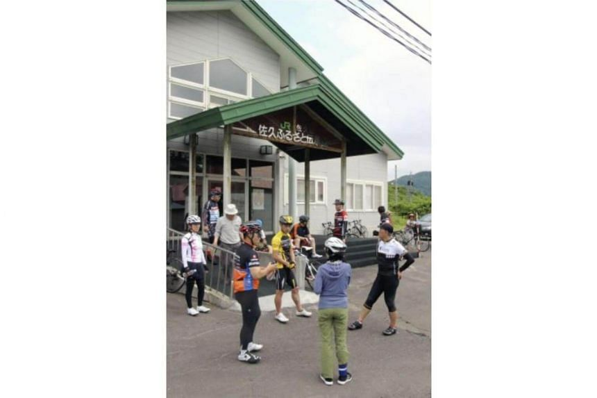 Bike enthusiasts rest in front of Saku Station on the JR Soya Line in Nakagawa, Hokkaido, on July 8.
