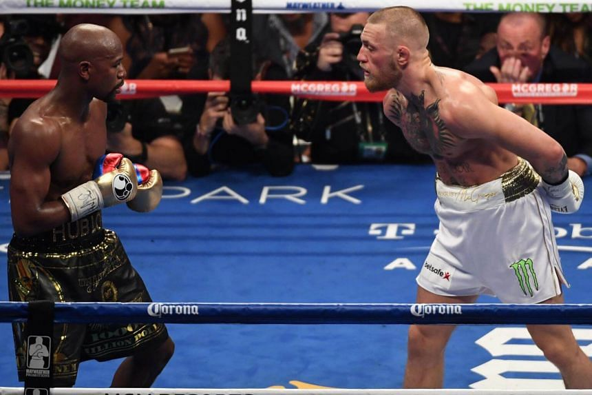 Conor McGregor (right) taunts Floyd Mayweather Jr. during their super welterweight boxing match on August 26, 2017 at T-Mobile Arena in Las Vegas, Nevada.