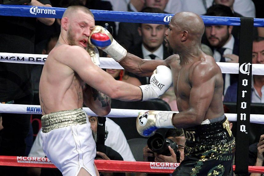 Boxer Floyd Mayweather Jr. (right) lands a right to the face of mixed martial arts star Conor McGregor during their fight at the T-Mobile Arena in Las Vegas, Nevada on Aug 26, 2017.