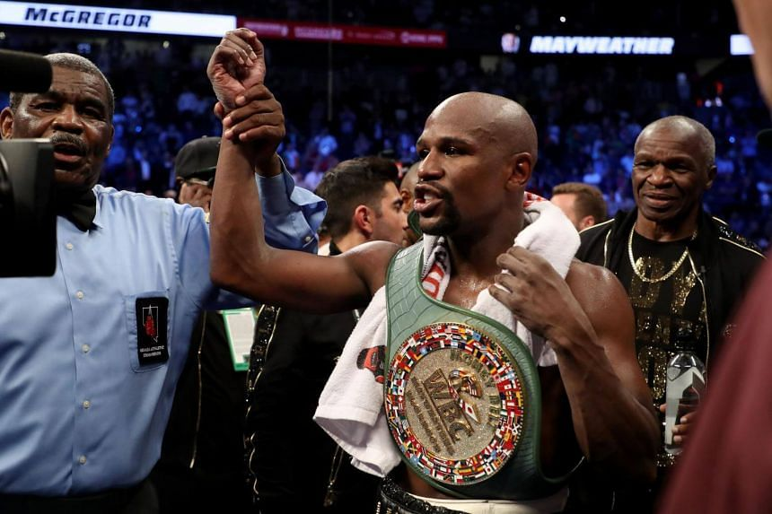 Floyd Mayweather Jr. celebrates with the WBC Money Belt after his TKO of Conor McGregor in their super welterweight boxing match at T-Mobile Arena in Las Vegas on Aug 26, 2017.