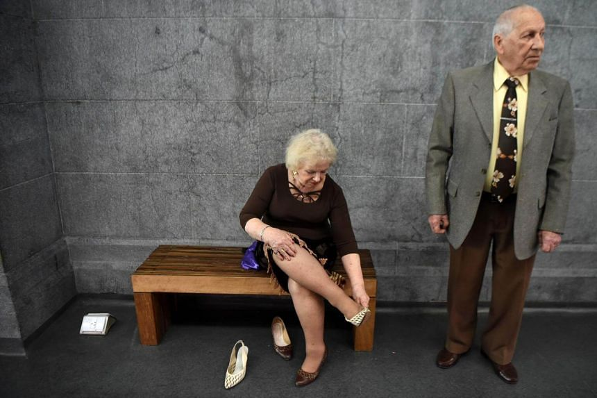Tango dancers Nina Chudoba (left), 82, and Oscar Brusco , 90, prepare to dance at a Milonga (a place or an event to dance tango) in Buenos Aires, on Aug 18, 2017.