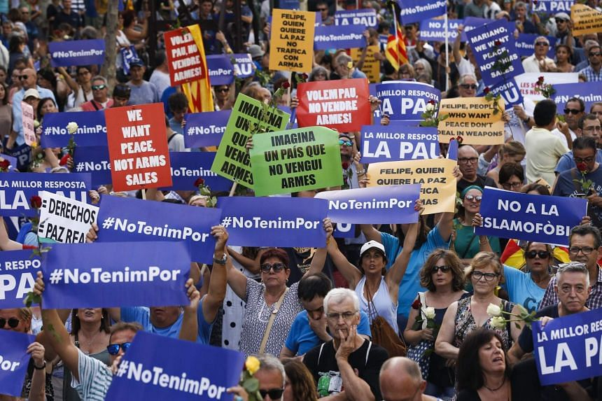 People hold placards and Catalan flags during the march against terrorism.