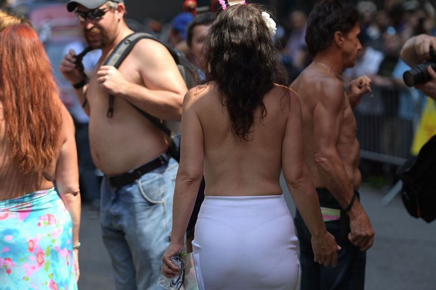 People attend the 10th annual GoTopless Day Parade in New York.