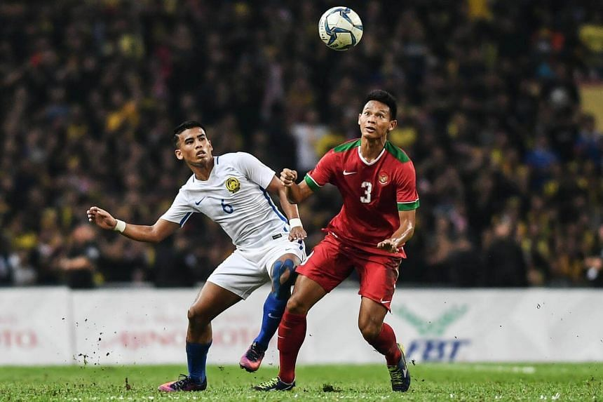 Malaysia's Safawi Rasid (left) fights for the ball against Indonesia's Andy Setyo Nugroho during their men's football semi-finals match at the 29th Southeast Asian Games (SEA Games) at Shah Alam Stadium in Shah Alam, on Aug 26, 2017.