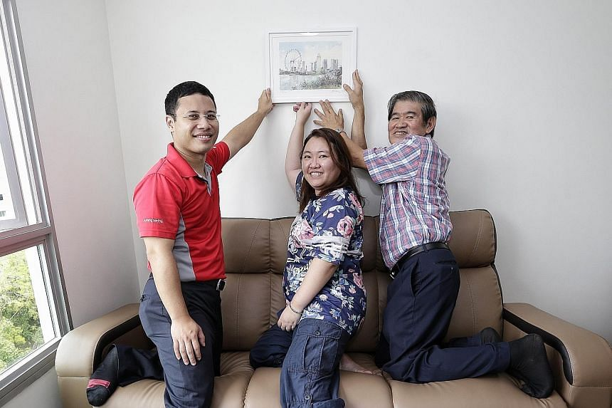 Member of Parliament Desmond Lee (left), home owner Esther Tan and artist Ong Kim Seng, with the print Ms Tan received.