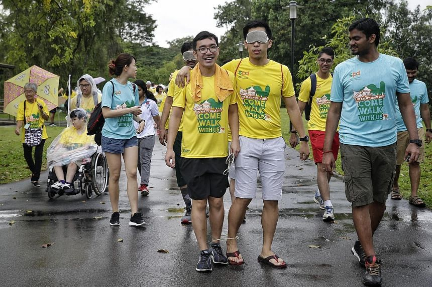 """A participant trying out an obstacle challenge by walking 200m both blindfolded and three-legged at the Chinese Garden yesterday during the 3km SPD Ability Walk, now in its second year. One participant found walking blindfolded """"scary""""."""