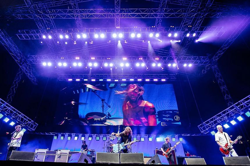 Foo Fighters, comprising (from left) Chris Shiflett, Rami Jaffee, Dave Grohl, Nate Mendel and Pat Smear, with Taylor Hawkins on the screen, rocking it at the National Stadium.