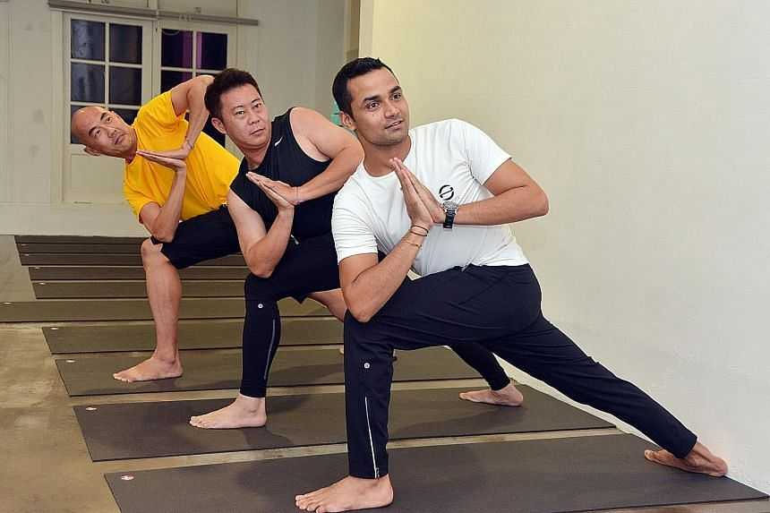 Mr Dev Kapil, director of One Wellness Fitness Club, and two of his male yoga students (from left) Andy Teo, 48, and Alex Lau, 43. Mr Dev attributes the increase in male yoga enrolment to research done over the years that has raised awareness about i