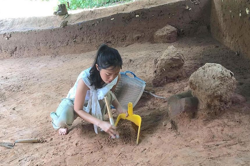 Above: Ms Khoo working in an excavation pit. Left: A close-up of the Buddha statue with a naga hood.