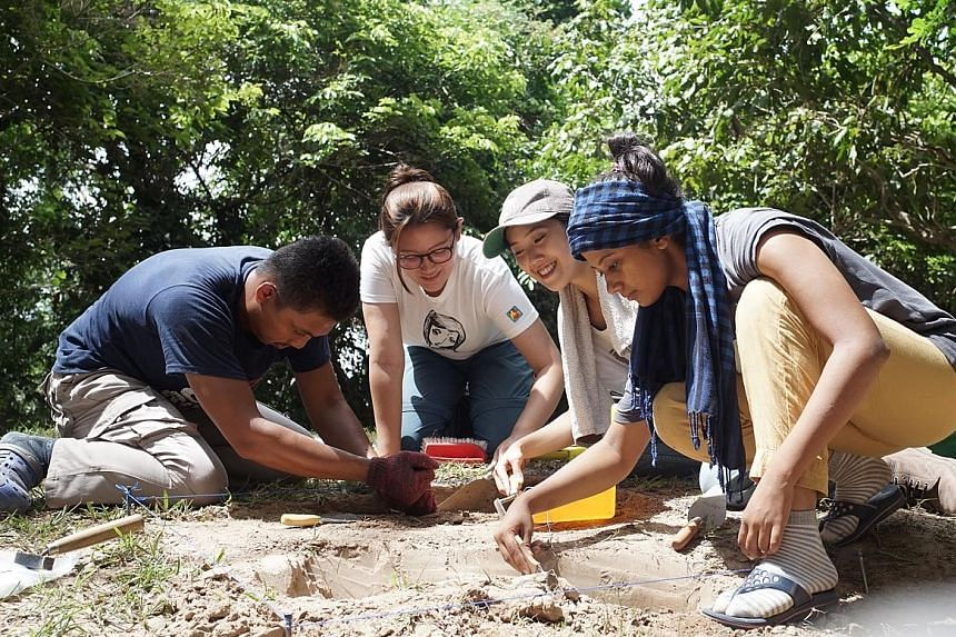 Above: Singaporean Natalie Khoo (second from right) and her teammates (from left) Indonesian Amir Husni, Filipina Anne Marie Valera and Indian Shaashi Ahlawat had been digging on a sloping mound when the statues started appearing. Left: The artefacts