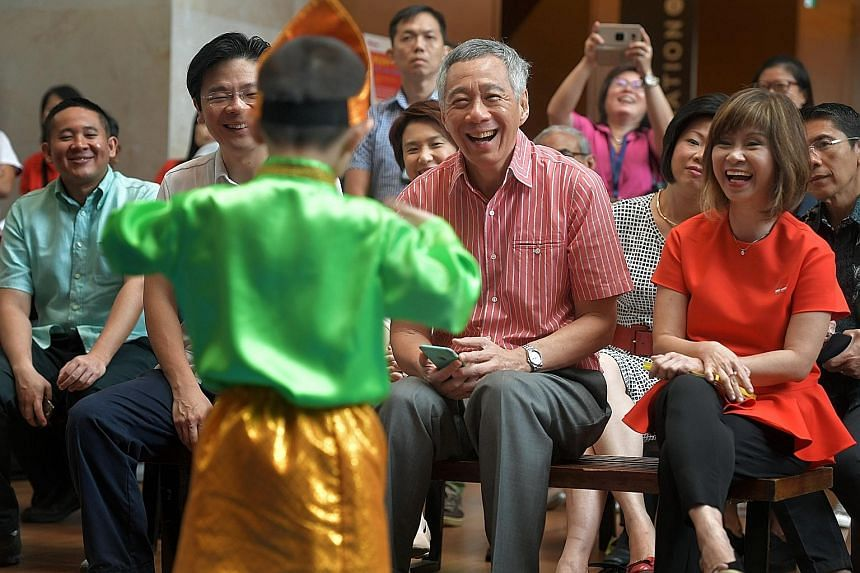 Above: Kindergarten children performing at the PCF Family Day held at the National Gallery Singapore yesterday. Below: Prime Minister Lee Hsien Loong, with National Development Minister Lawrence Wong and Senior Minister of State for the Environment a