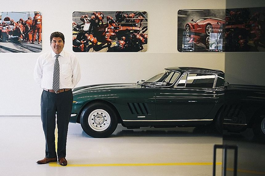 A forest green Ferrari 275 parked next to Mr Steven Posner, chief executive of Putnam Leasing, at its showroom in Greenwich, Connecticut.