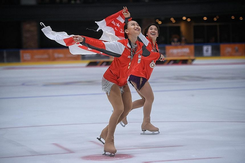Gold medallist Yu Shuran (left) celebrates with compatriot Chloe Ing as they skate around the ice rink at the Empire City Mall after the women's figure skating competition yesterday.
