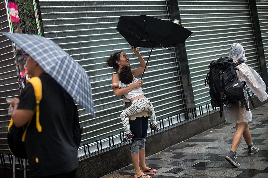 Pedestrians in Hong Kong's Tsim Sha Tsui area yesterday coping with rain and wind caused by tropical storm Pakhar. Hong Kong and Macau raised a Typhoon 8 signal early yesterday but lowered it to No. 3 by the afternoon.
