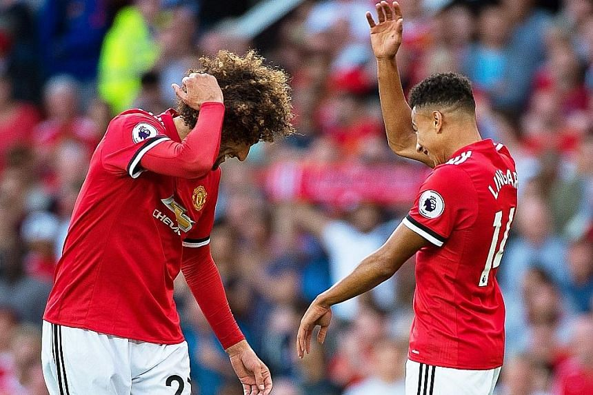 Manchester United substitutes Marouane Fellaini (left) and Jesse Lingard celebrate after the Belgian gave the hosts a 2-0 lead over Leicester City in the Premier League. Lingard set Fellaini up, allowing United to maintain their perfect start.