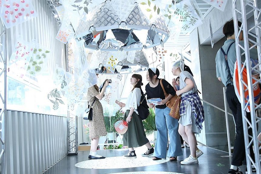 Visitors at the Singapore: Inside Out exhibition checking out the aural-visual showcase Each Sound Is A Flower (above).