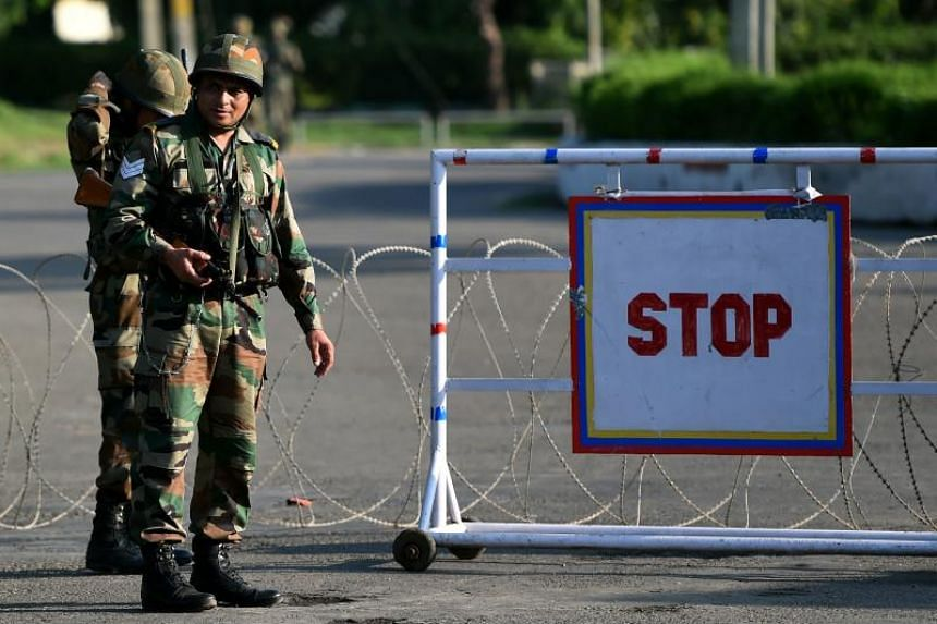 Indian soldiers stand guard at a checkpoint at Panchkula on Aug 26, 2017, a day after followers of controversial guru Ram Rahim Singh went on a rampage after their spiritual leader was convicted of rape.