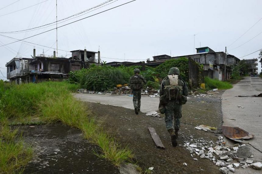 This photo taken on July 22, 2017 shows Philippine troops patrolling a deserted neighbourhood in Marawi.