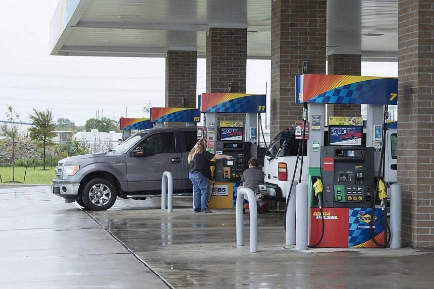 Customers fuel vehicles at a Sunoco LP gas station ahead of Hurricane Harvey in Texas City, Texas, on Aug 25, 2017.
