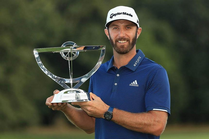 Dustin Johnson poses with the trophy after defeating Jordan Spieth to win The Northern Trust at Glen Oaks Club on Aug 27, 2017.