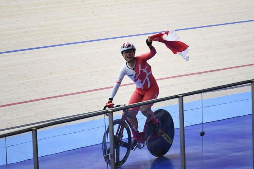 Calvin Sim holds Singapore's flag after winning the men's omnium cycling event at the SEA Games on Aug 28, 2017.