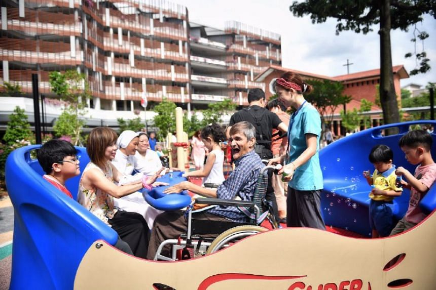 Elderly residents of St Joseph's Home in Jurong West playing with children. ST PHOTO: ARIFFIN JAMAR