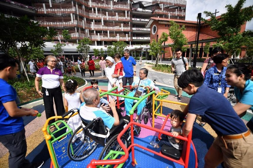 Elderly residents of St Joseph's Home in Jurong West playing with children on the merry-go-round.