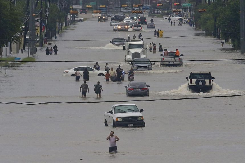 People walk through the flooded waters of Telephone Road in Houston as the city battles with tropical storm Harvey and resulting floods, on Aug 27, 2017.