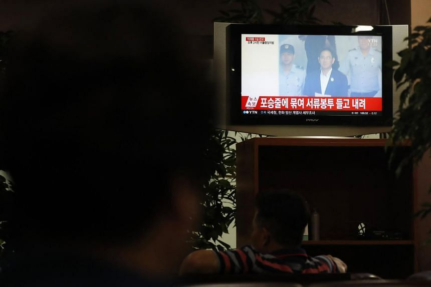 A South Korean woman watches a news broadcast on vice-chairman of Samsung Group Lee Jae Yong's final trial on Aug 25, 2017.