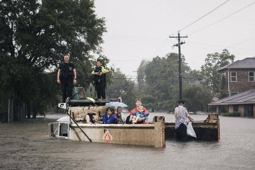 Rescue workers and civilians wait for emergency crews in Houston, on Aug 27, 2017.