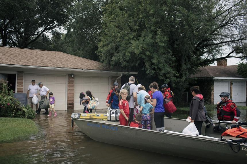 Police officers bring a family to dry land as they wait for an amphibious vehicle to pick them up in Houston, on Aug 27, 2017.